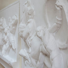 Wall sculpture of Greek gods, one holding up a shield