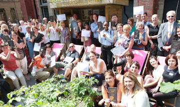 A large group of staff sat in a garden holding certificates and awards
