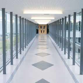 A brightly lit glass corridor leading to a door