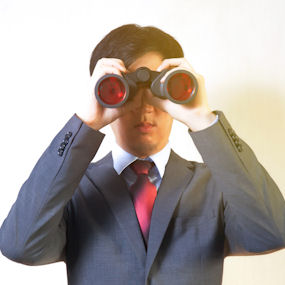 A man in a suit looking through a pair of binoculars