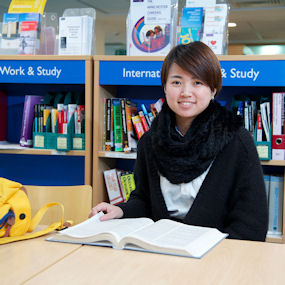 Female student sat with a book open in front of her smiling to camera