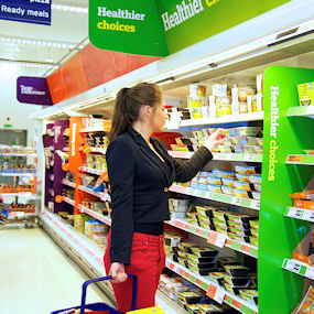 A young woman in a supermarket buying from an aisle marked 'healthier choices'