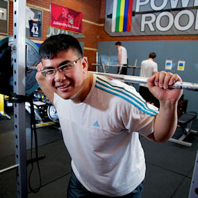 Asian man lifting weights in a gym
